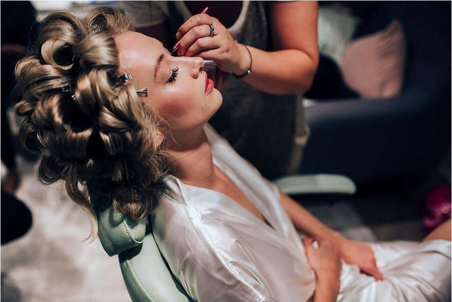 makeup artist applying individual eyelashes to bride with natural makeup