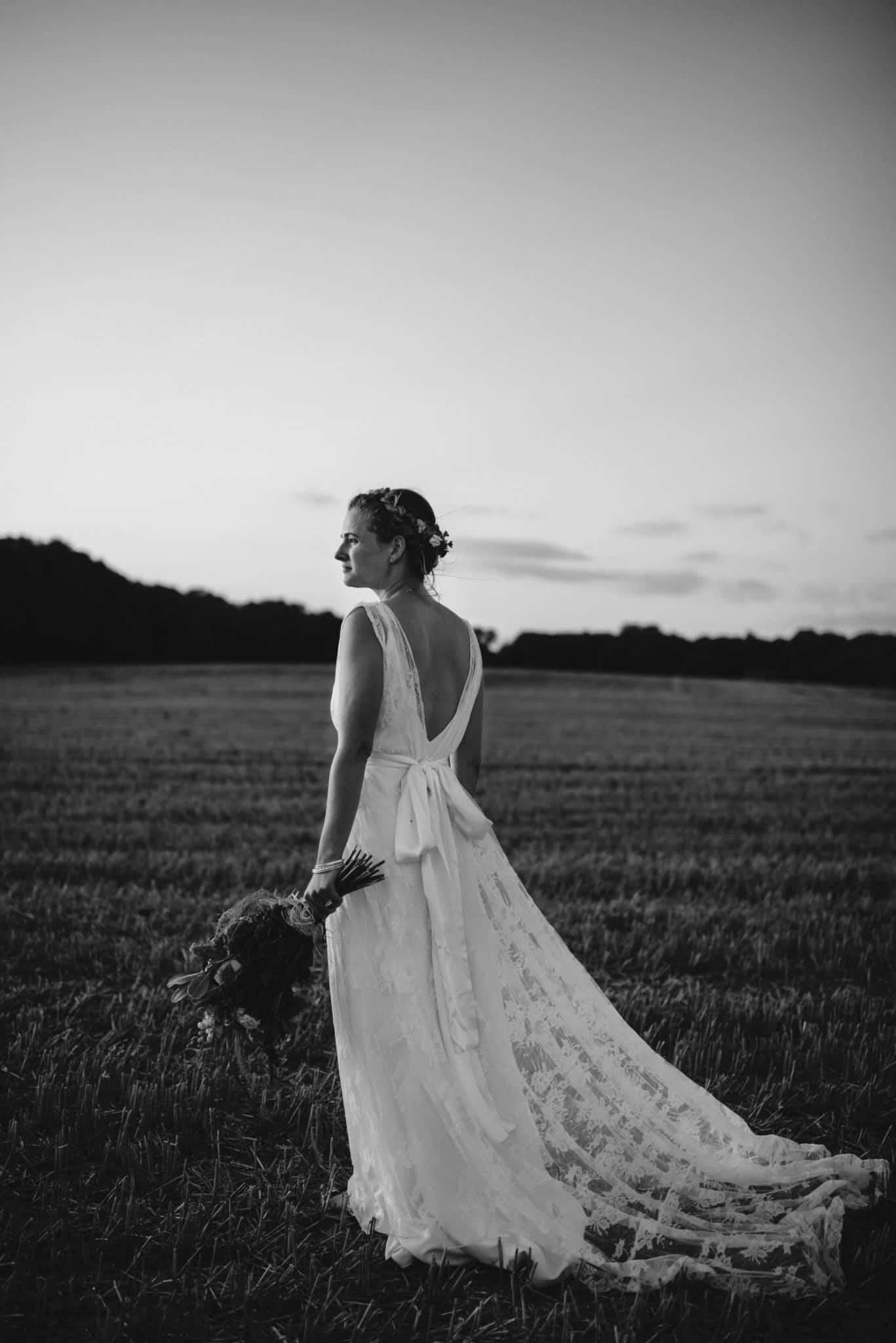 back of boho bride walking through field