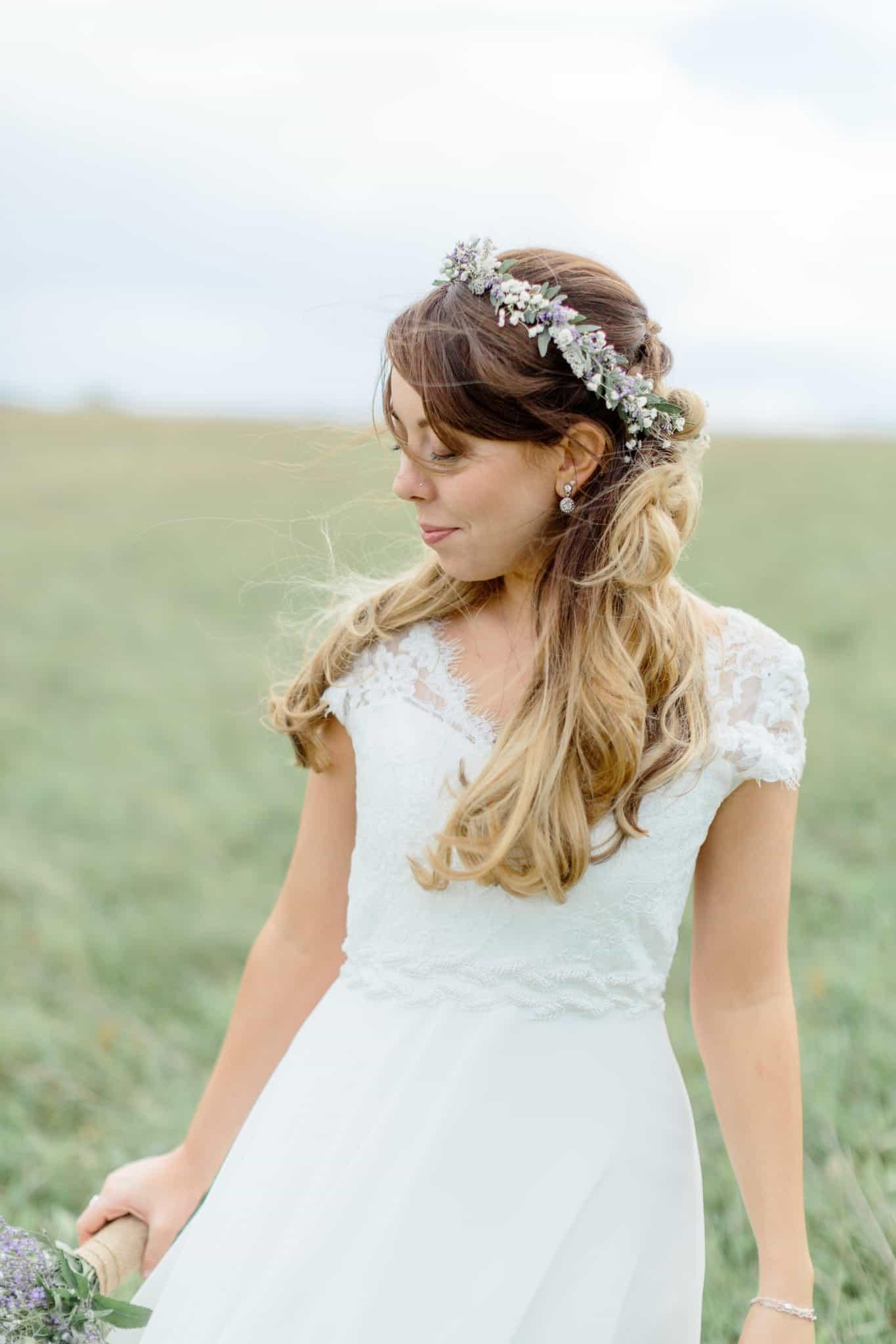 boho bride with flower crown in field