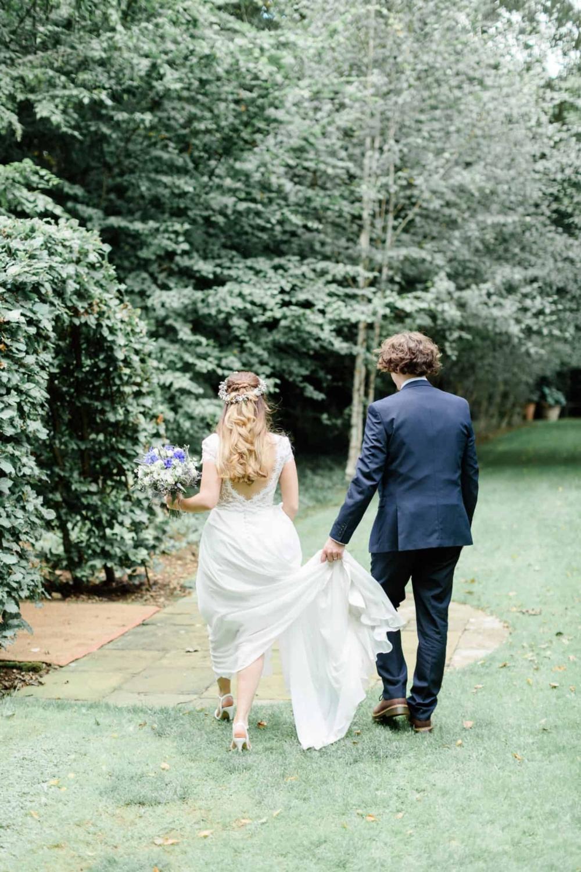 back of bride and groom walking in garden