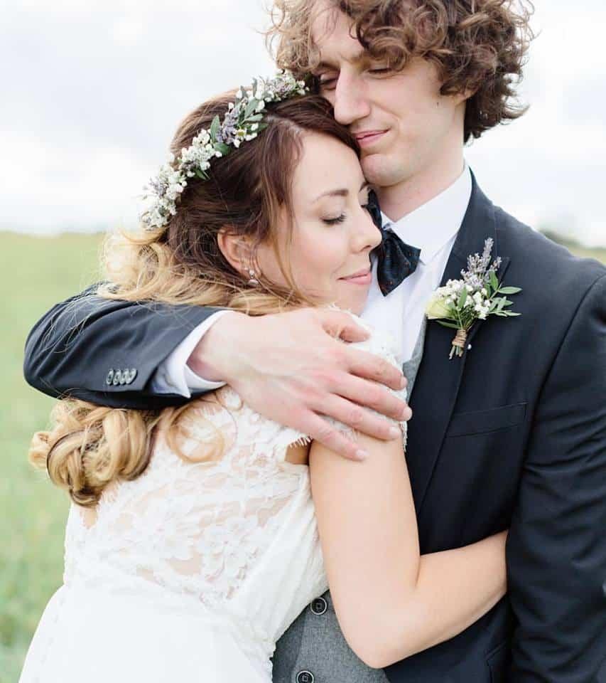 groom embracing bride with flower crown