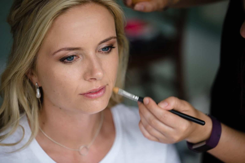 makeup artist applying makeup to bridesmaid