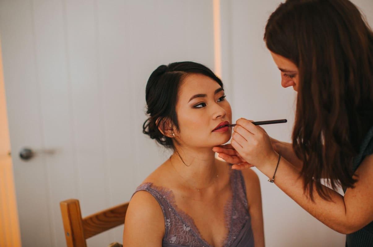 makeup artist applying lipstick to bridesmaid