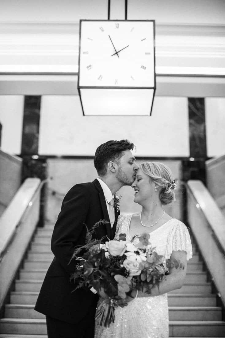 groom kisses vintage inspired bride under clock