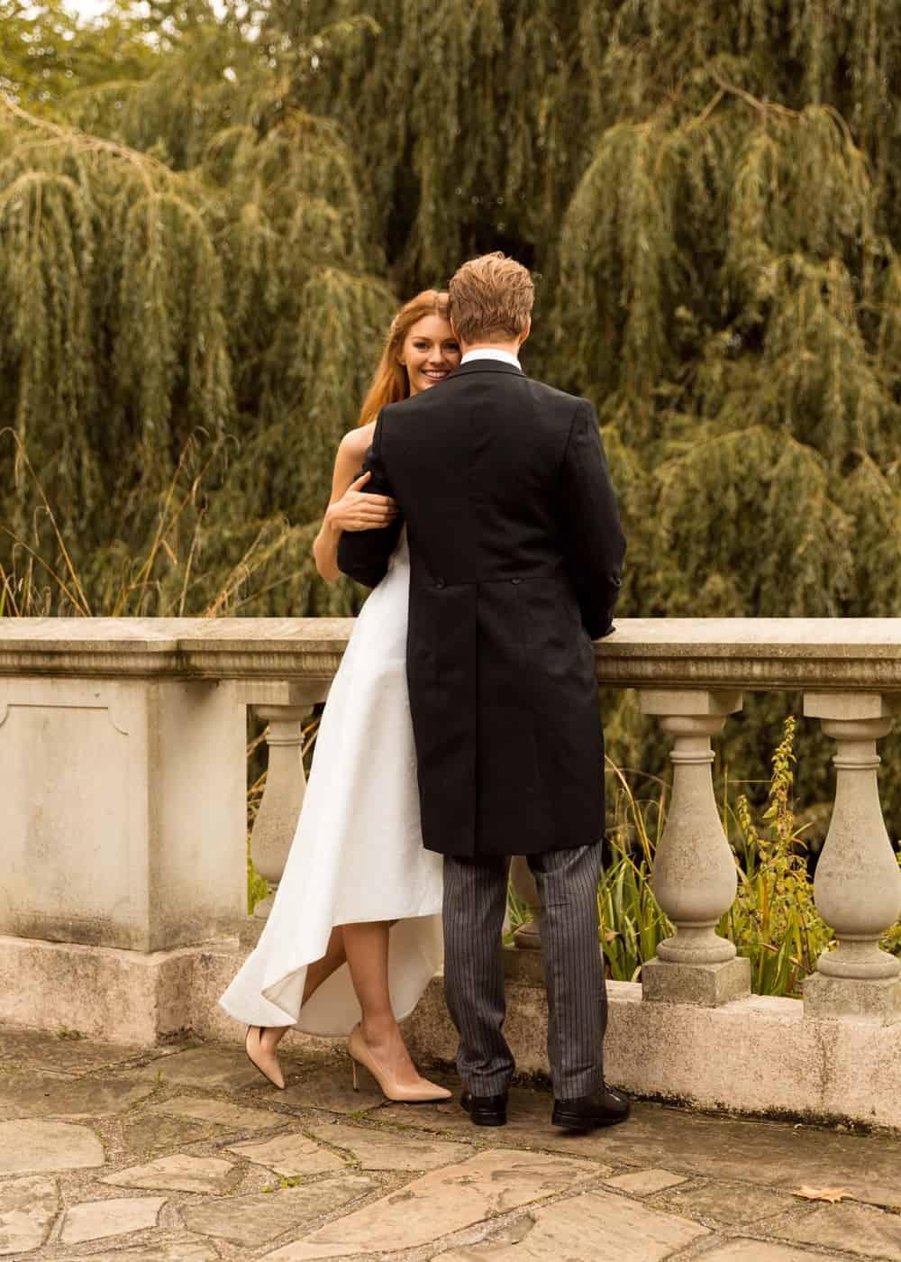 happy bride and groom standing next to bridge