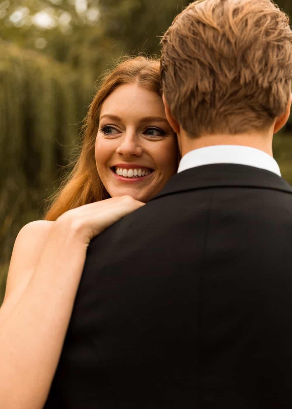 happy bride with head on grooms shoulder
