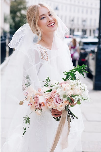 laughing bride on streets of london holding bouquet