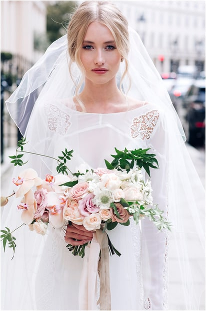 beautiful bride on streets on london holding bouquet