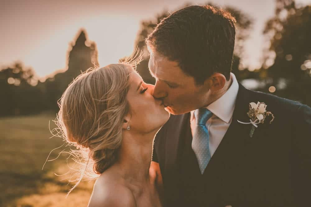photograph of bride and groom kissing at sunset on their wedding day