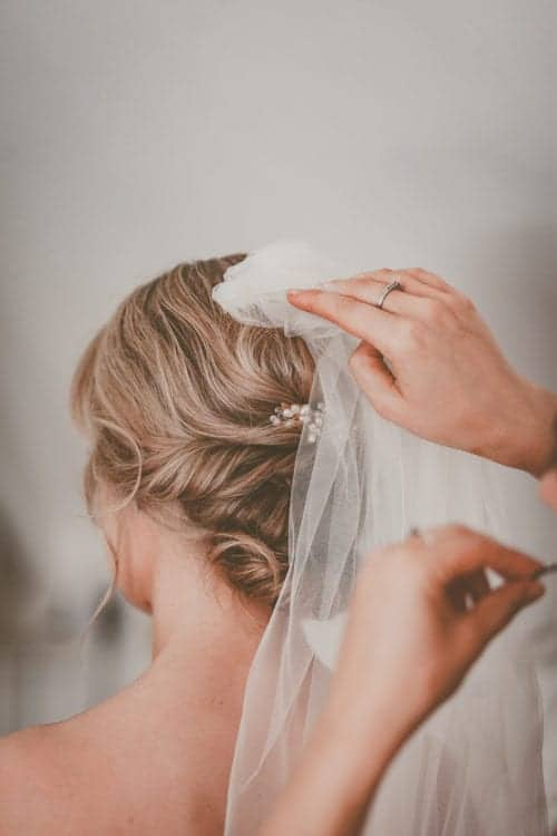 hairstyling attaching veil to bride with romantic updo
