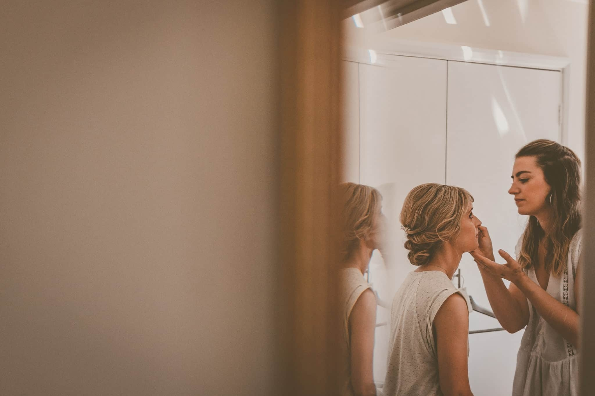 makeup artist applying makeup to bride with loose updo