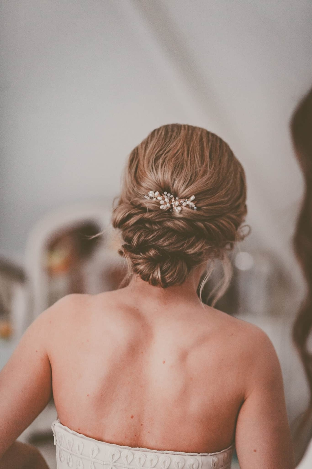 twisted updo on bride with pearl hair accessory