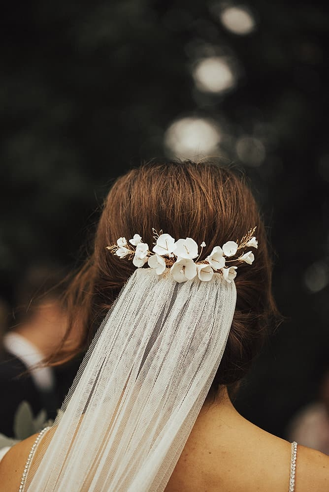 close up of bridal updo with veil and porcelain flower hair accessory