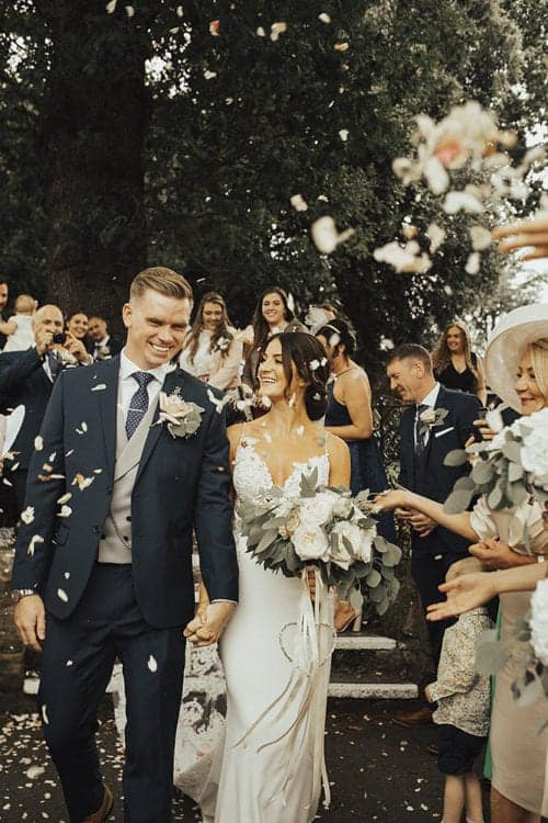 bridal party throwing confetti on bride and groom after wedding ceremony