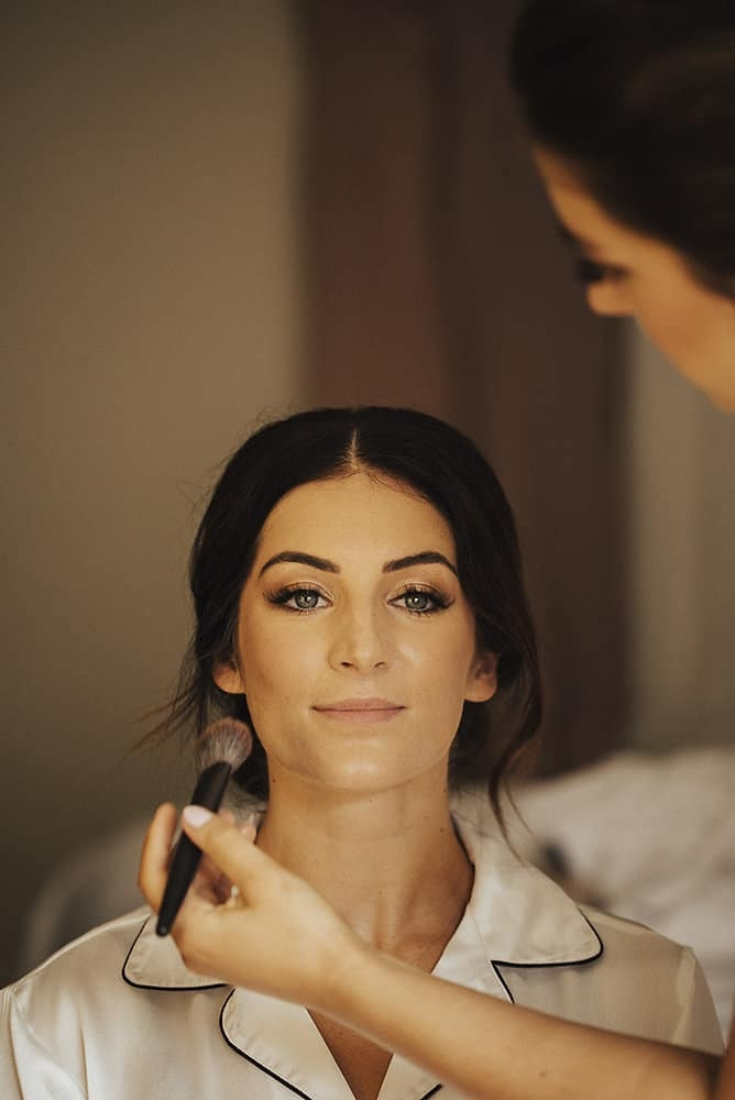 portrait of bride having her makeup applied before wedding ceremony
