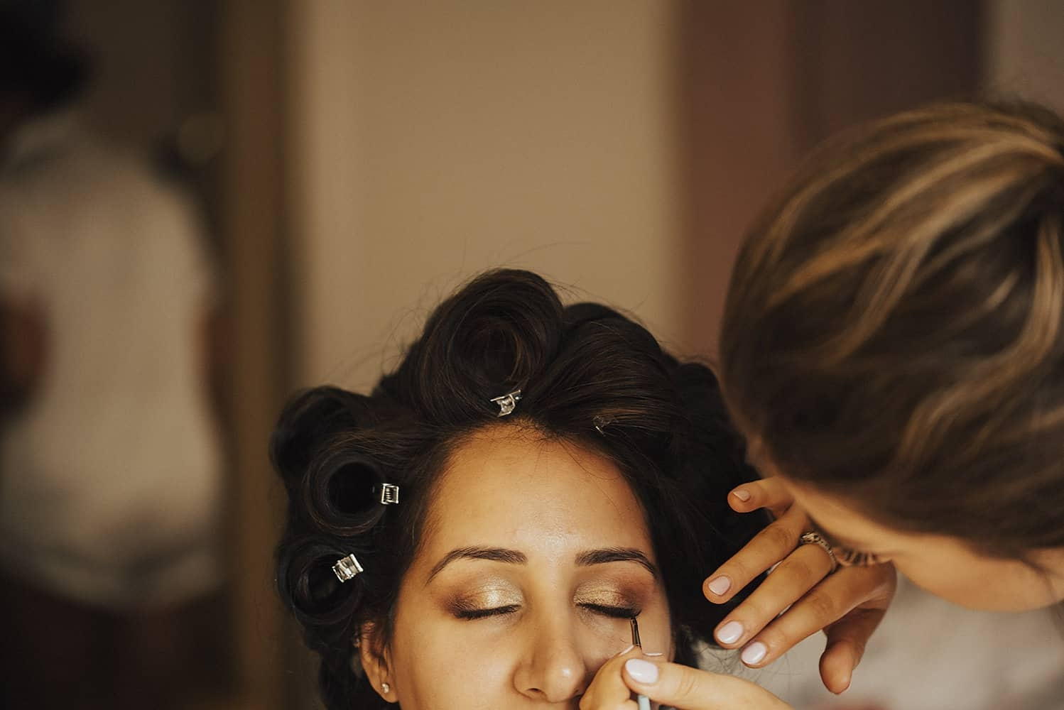 close up of makeup artist applying indivual eyelashes to bridesmaid with hair rollers