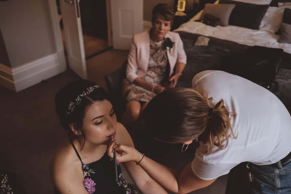 mother of the bride watching on a makeup artist applied lipstick to bride