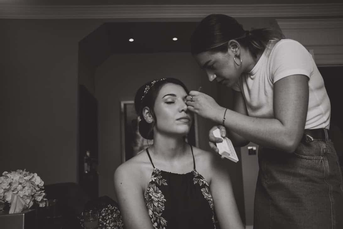 makeup artist applying individual eyelashes to bride
