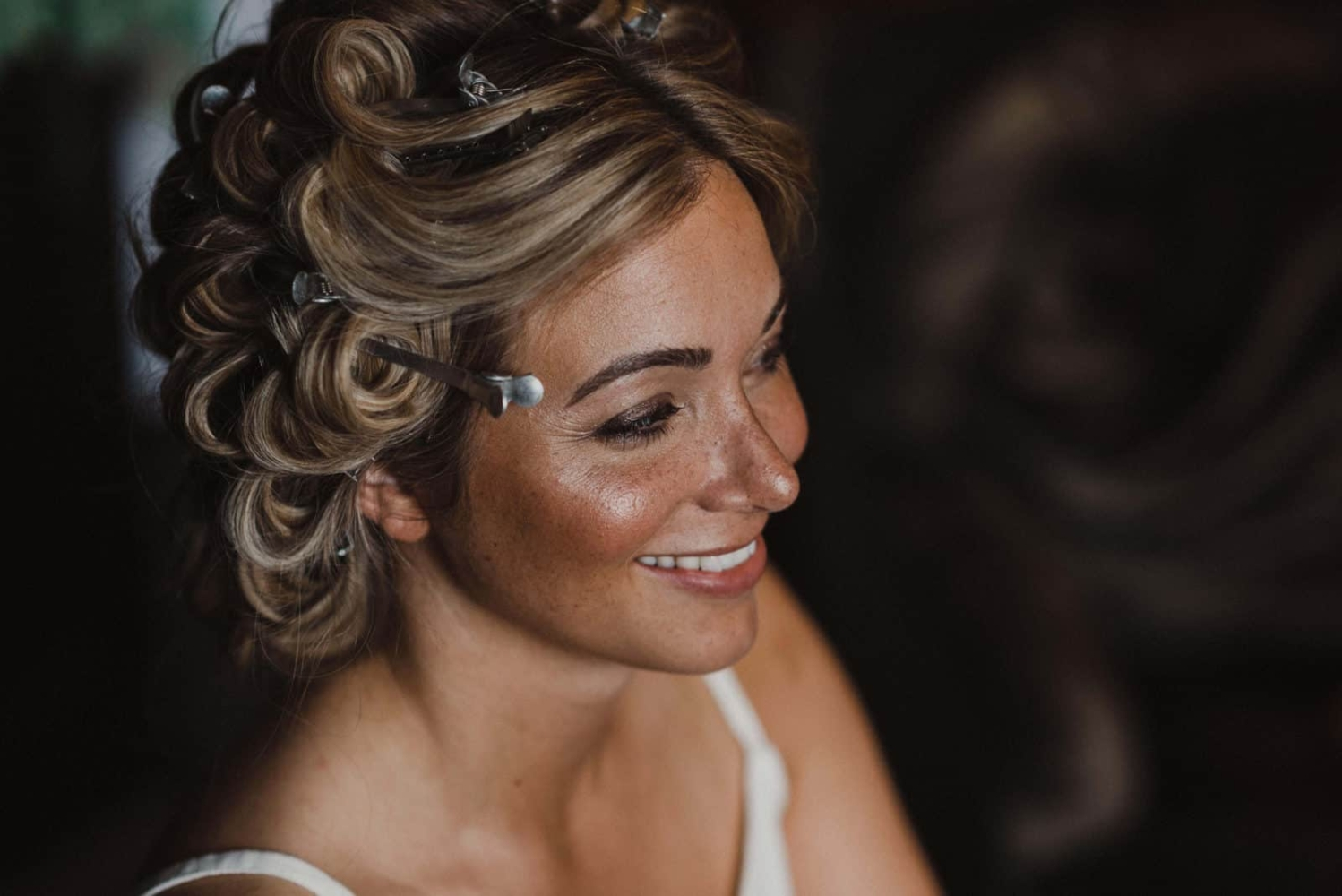 happy bride with natural makeup and hair rollers preparing for wedding ceremony