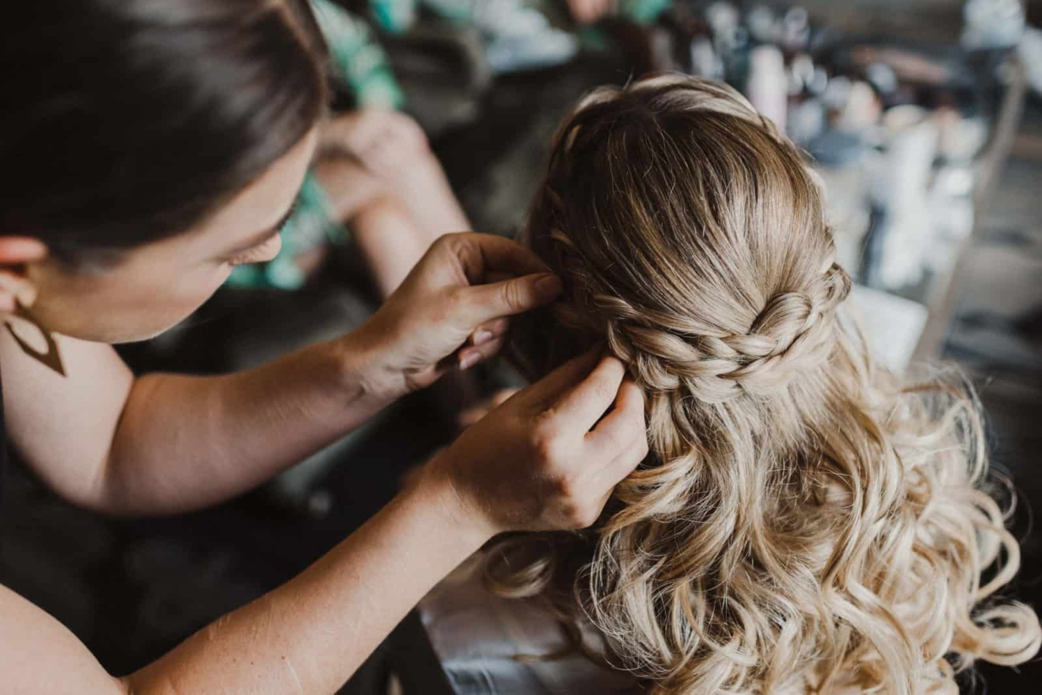 hairstylist braiding bride's hair