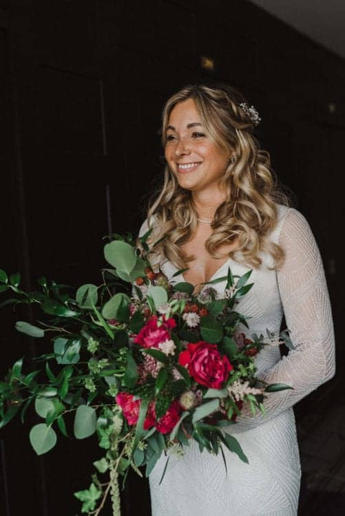 happy bride with loose curls holding large bouquet