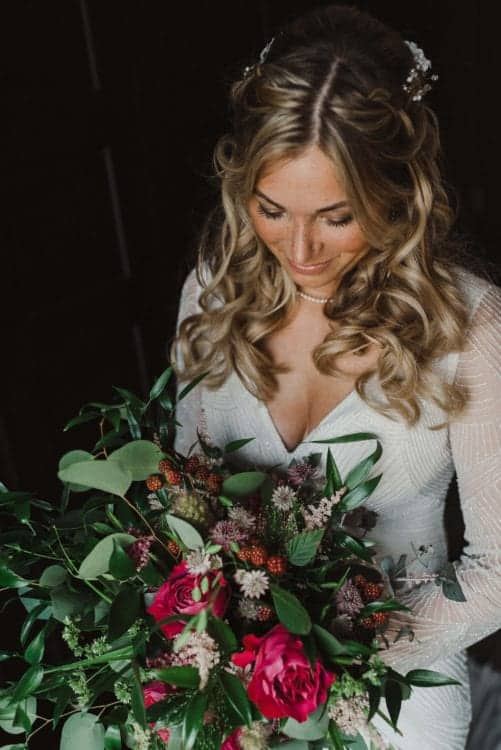 bride with braids and curls holding large bouquet