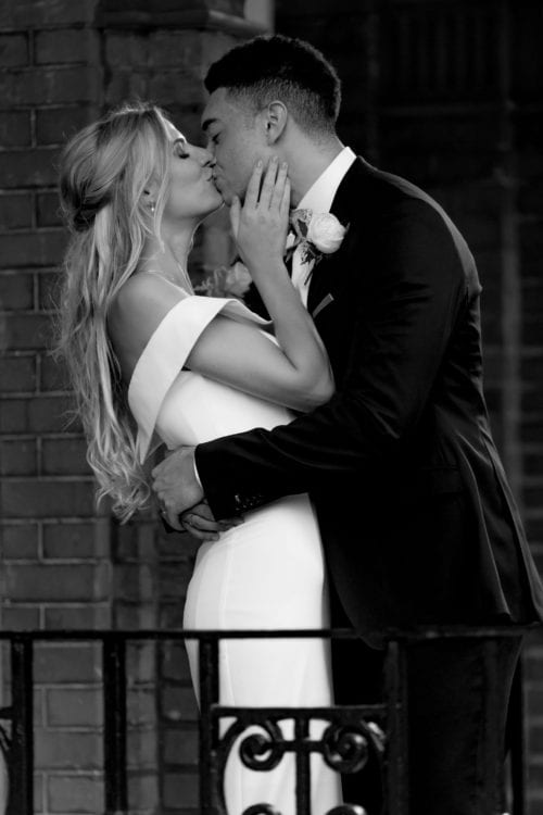 black and white photograph of bride and groom kissing
