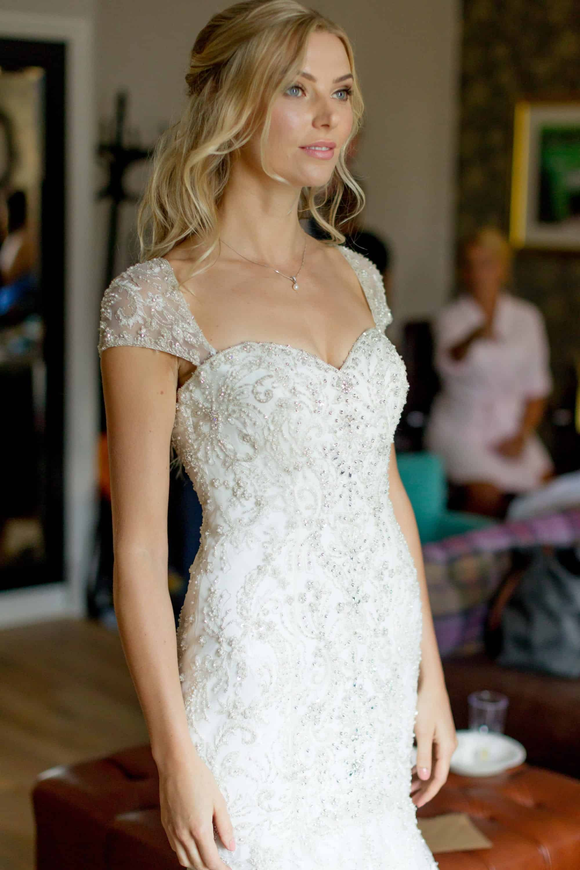 bride with half updo and natural makeup in a beaded wedding dress