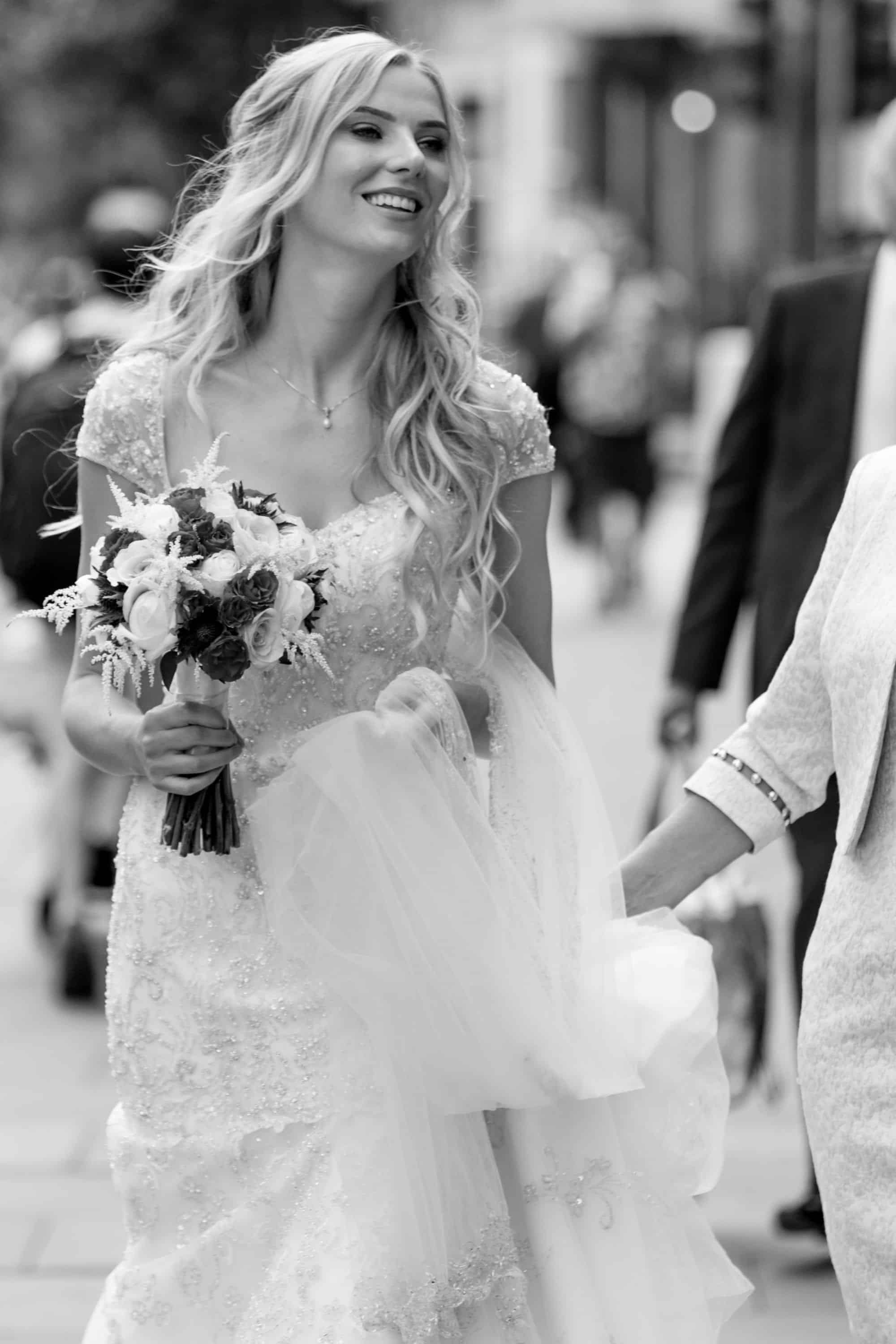 happy bride with loose curls walking through london