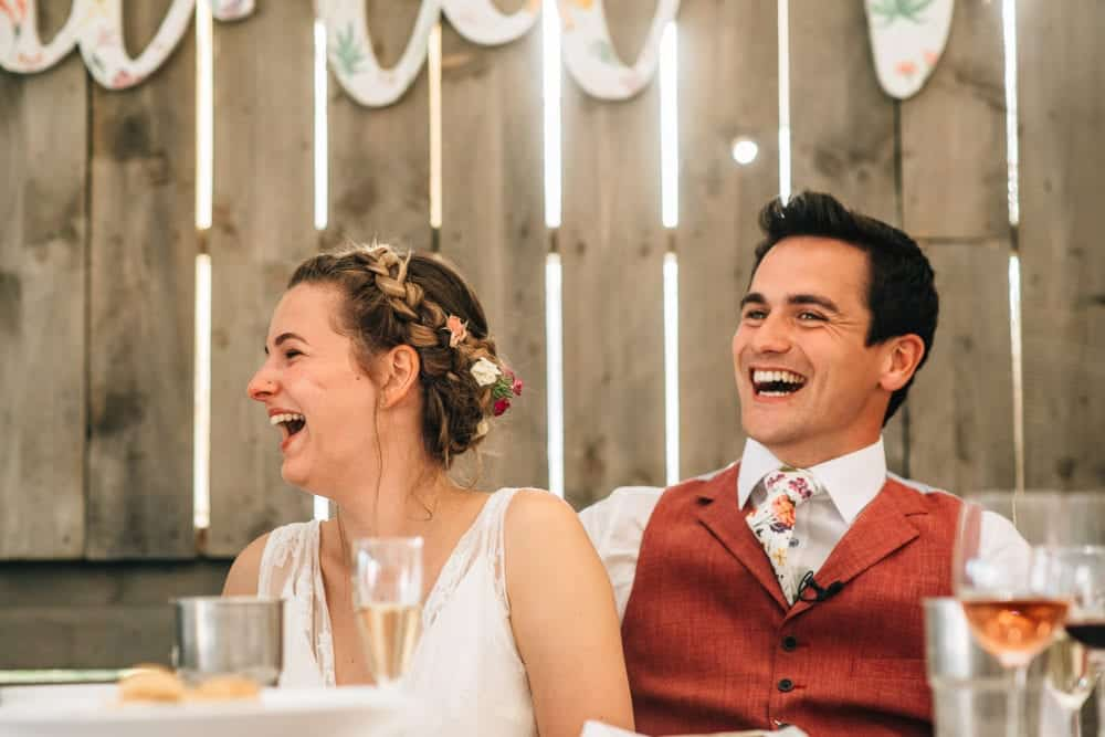 laughing bride and groom at festival wedding reception