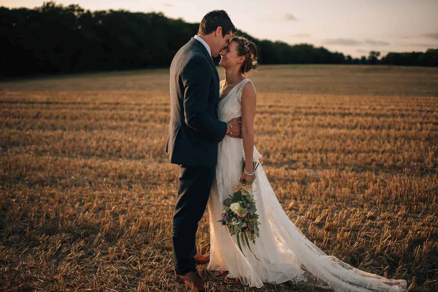 boho bride and groom photographed in field at sunset
