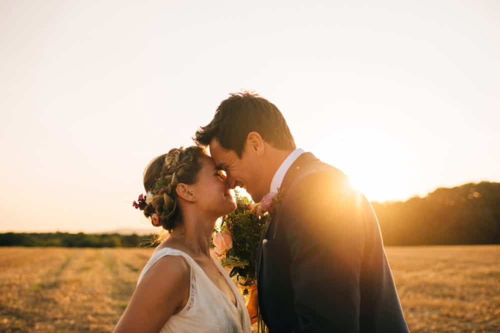 boho bride with crown braid and groom at sunet in field