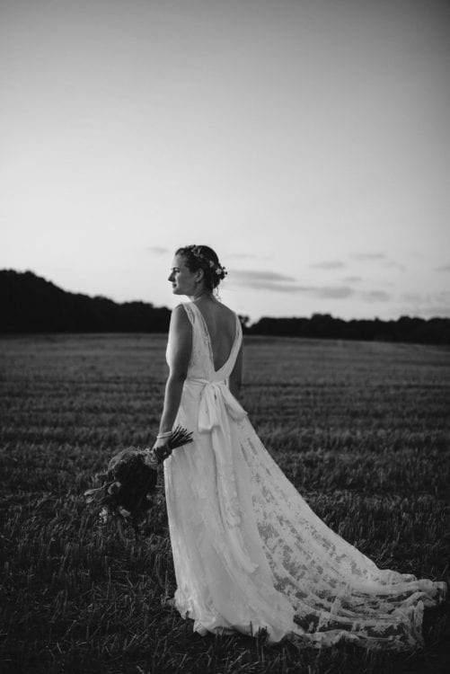 back of boho bride walking through field