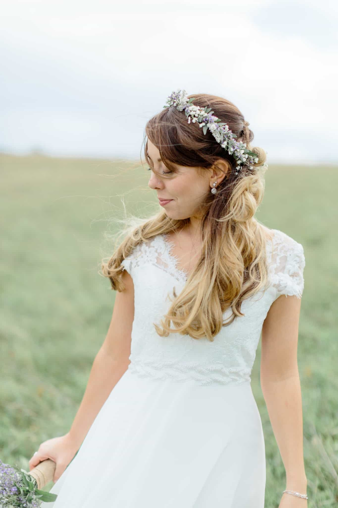 boho bride with flower crown in field