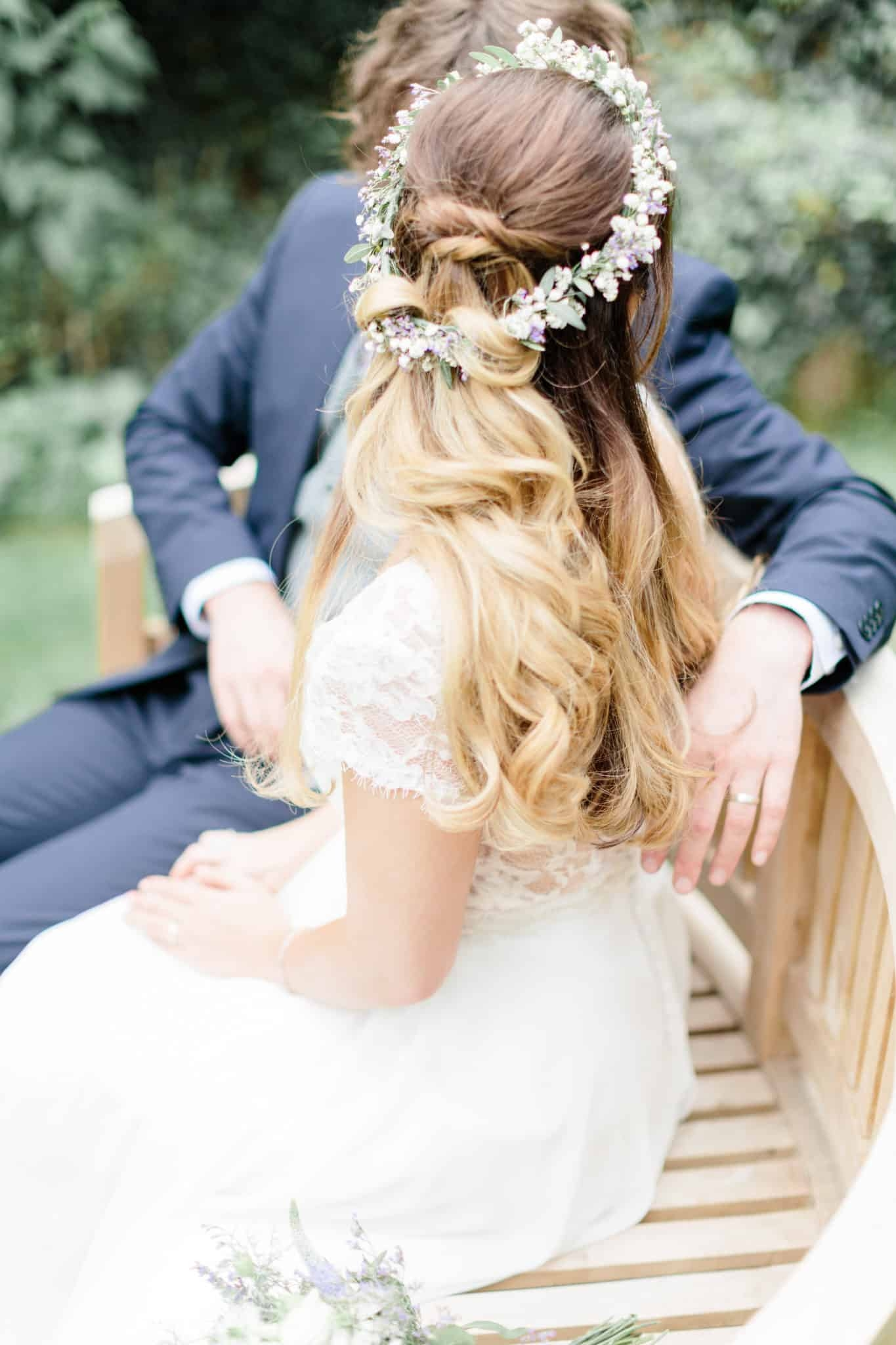 boho bride with flower crown and groom sitting on bench