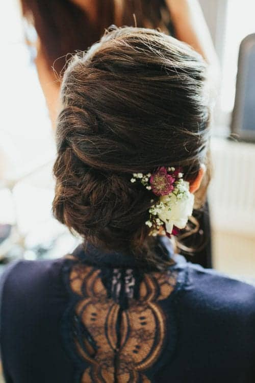 bridal updo with flower hair accessory