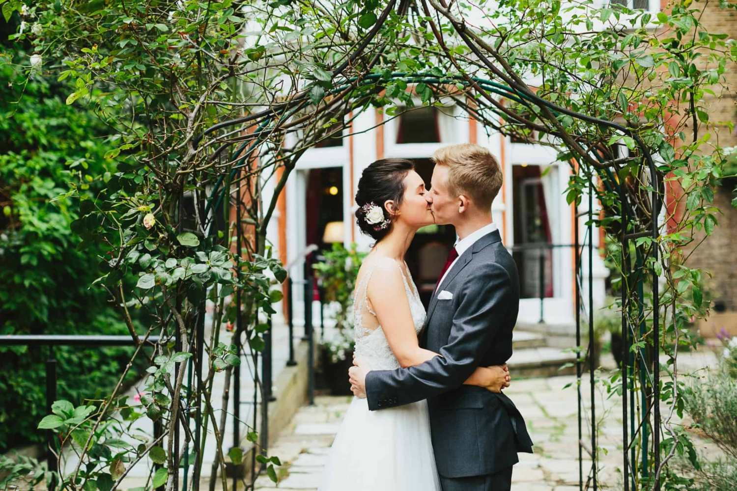 bride and groom kissing under vine archway