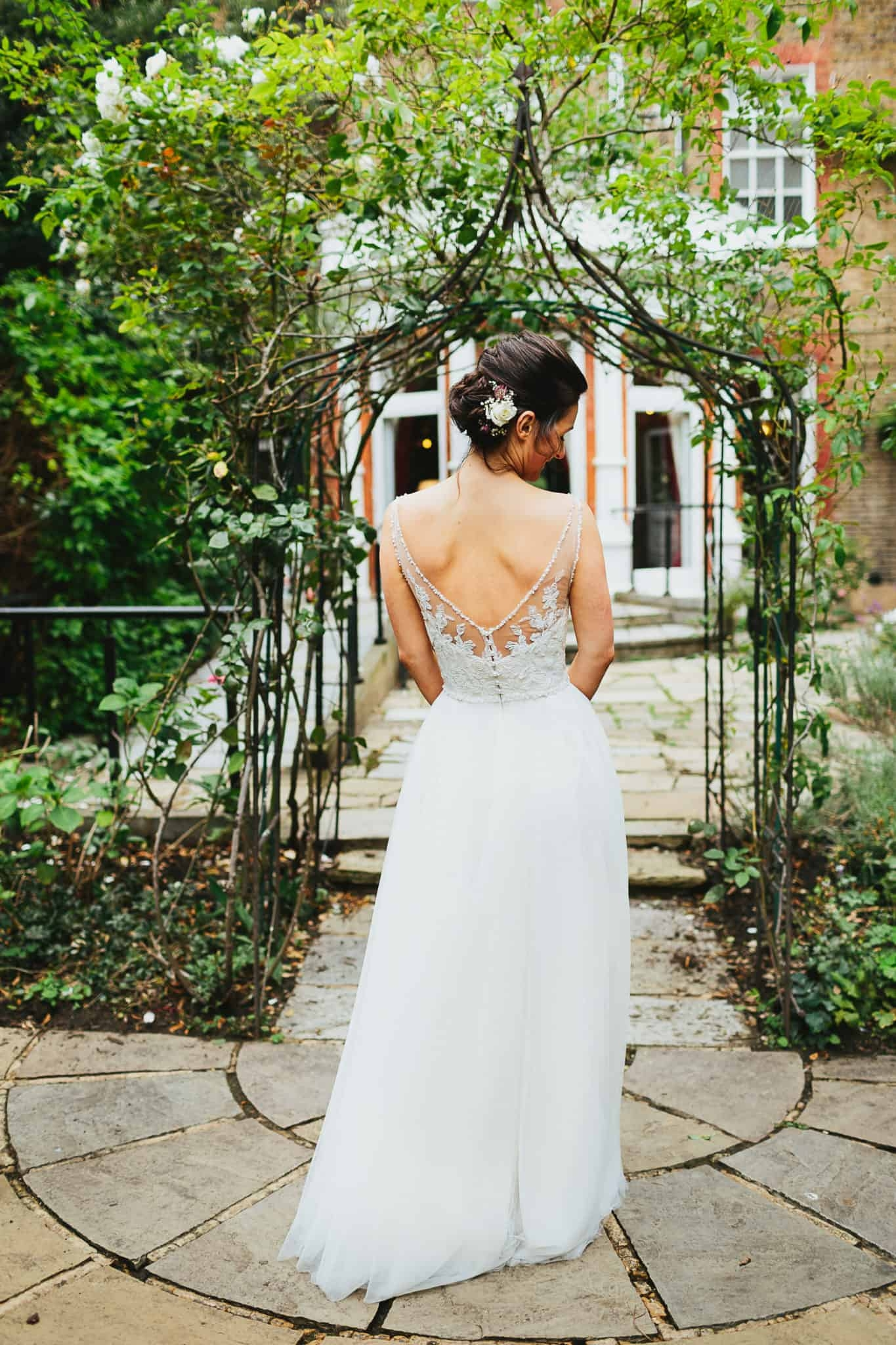 back of bride next to vine archway