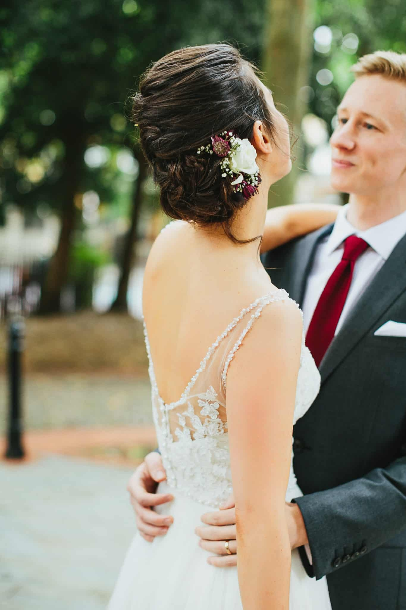 bride with updo and fresh flower accessory embracing groom