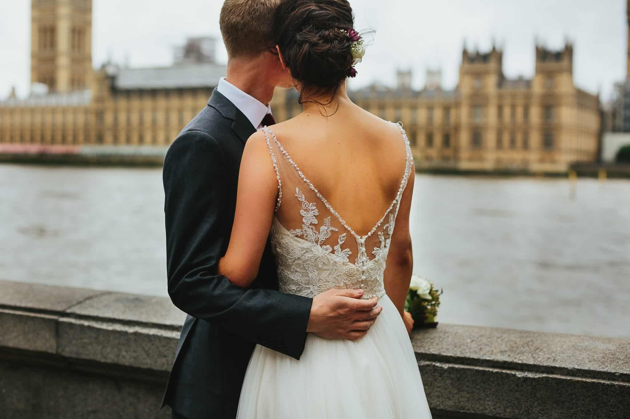 bride and groom looking out over river thames