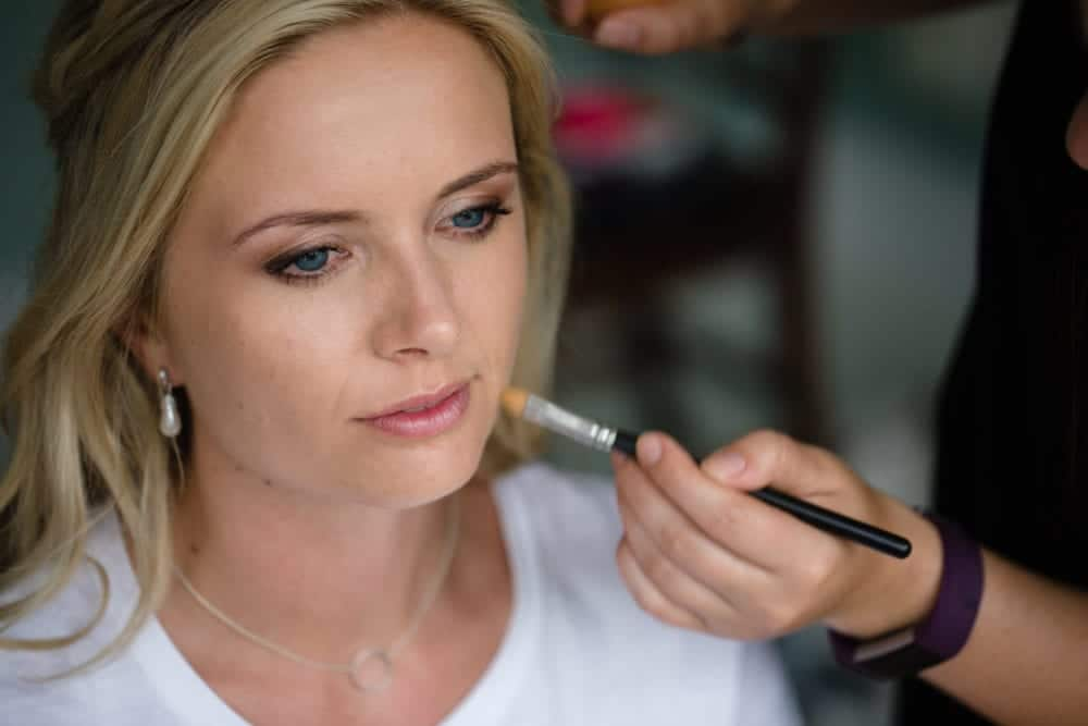 makeup artist applying makeup to bridesmaid