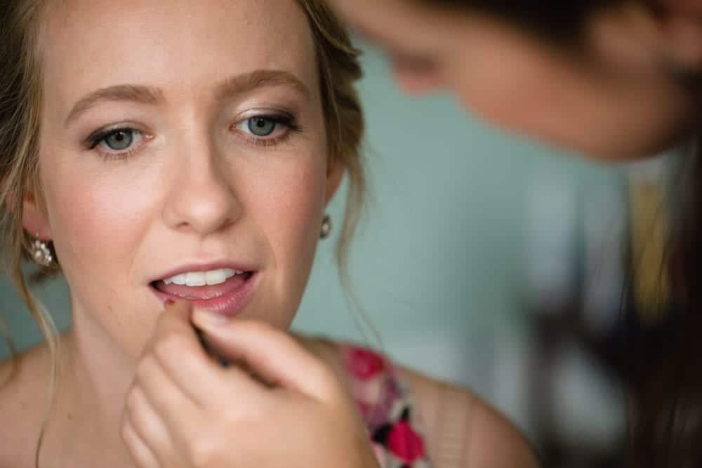 close up of makeup artist applying lipstick to bride