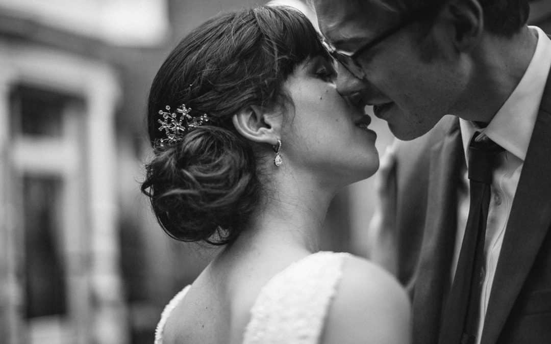 black and white photography of bride and groom kissing