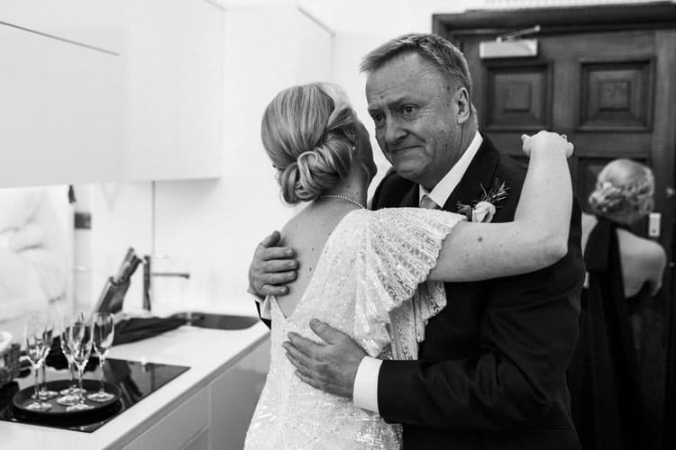 bride and father embracing in kitchen