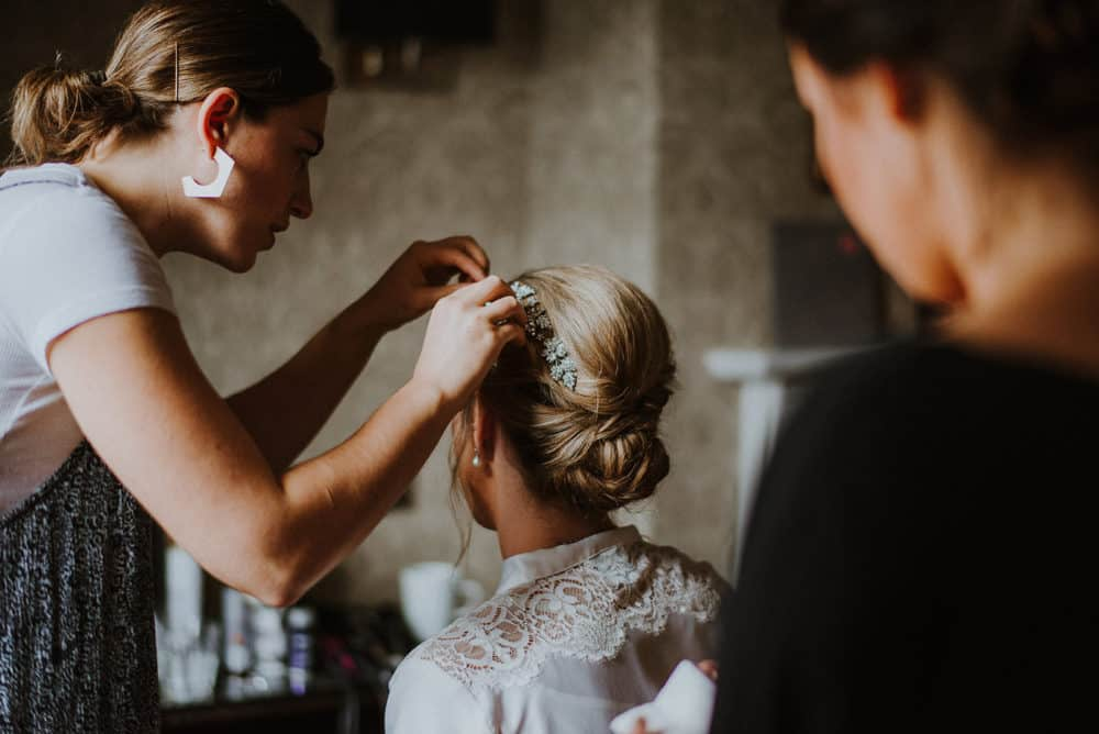 hairstylist securing bride's hair accessory