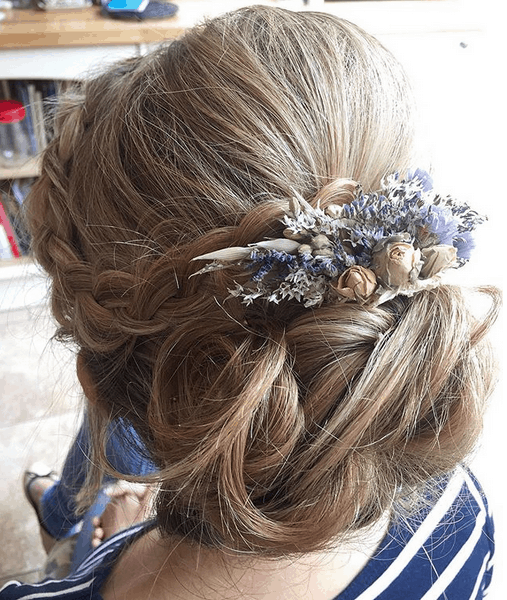 close up of bridal updo with braid and flower hair accessory