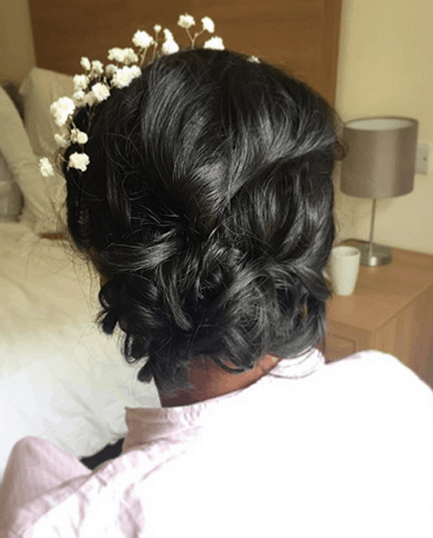 close up of loose bridal updo with baby's breath