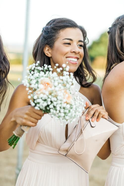 happy bridesmaid holding bag and bouquet
