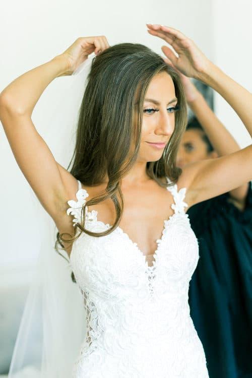 wedding hairstylist placing veil in bride's hair