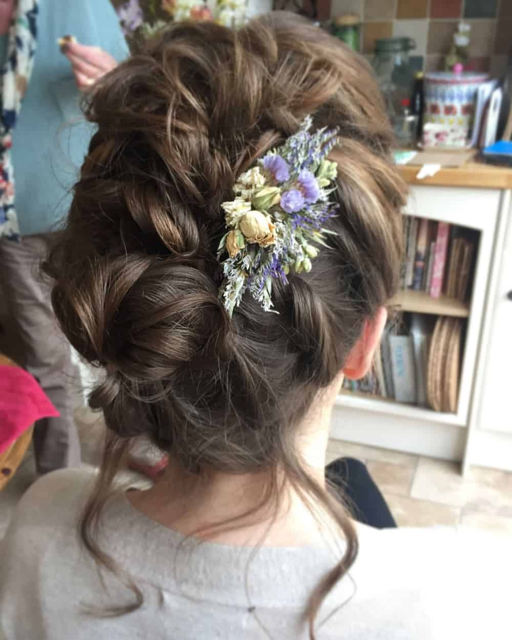 close up of twisted boho updo with floral hair accessory